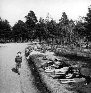 Boy walking past corpses, Bergen-Belsen. photo by George Roger